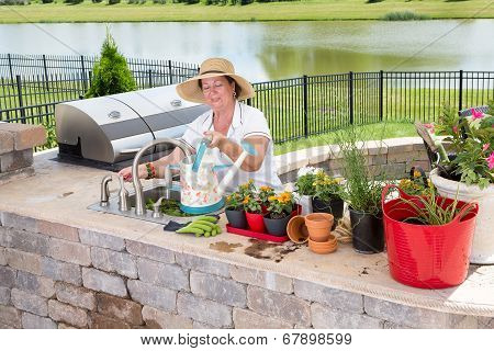 Elderly Lady Tending To Her Potted Plants