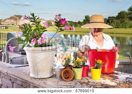 Elderly Lady Tending To Her Pot Plants On A Patio