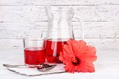 stock photo of hibiscus  - Cold hibiscus tea in glass jug with hibiscus flower on wooden background - JPG