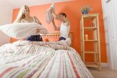picture of shelving unit  - Young couple facing each other kneeling on bed having a pillow fight - JPG