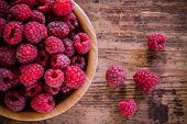 pic of fruit bowl  - bright fresh organic raspberries in a bowl on old wooden background - JPG