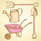 stock photo of hand-barrow  - Garden fork barrow watering can and shovel vintage background - JPG