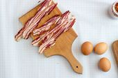 stock photo of bacon strips  - Bacon cut into strips and eggs on a tabletop overhead view - JPG