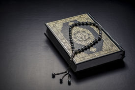 pic of islamic religious holy book  - Islamic Book Holy Quran and Beads on Black Background - JPG