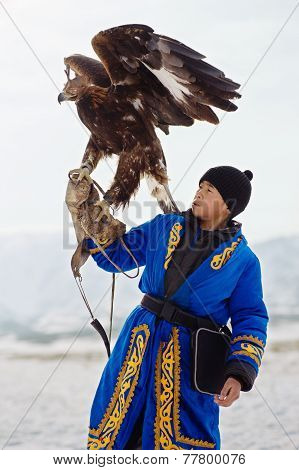 NURA KAZAKHSTAN - FEBRUARY 23: Eagle on kid's hand in Nura near Almaty on February 23 2013 in Nura