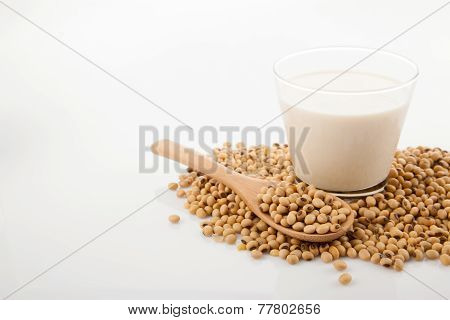 Soy Milk In Glass With Soybeans And Wooden Spoon