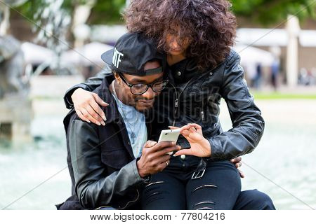 African American man sitting with girlfriend at fountain showing message on mobile phone or looking up information
