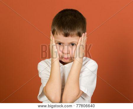 grimacing boy portrait on brown background