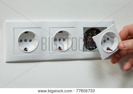 A young electrician installing an electrical plug in a new house.
