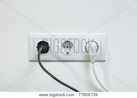 Black and white power plugs plugged in a white socket