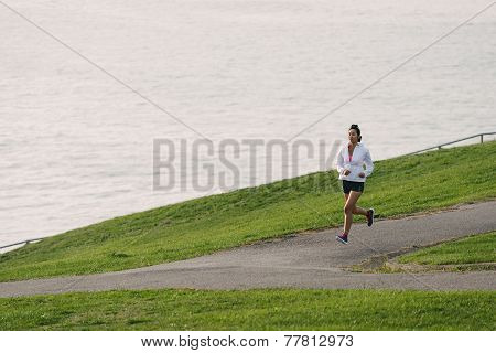 Woman Running In Park By The Sea