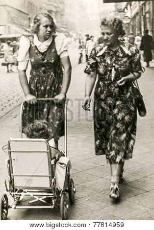 GERMANY, CIRCA 1940s: Vintage photo of two women walking dawn the street with a baby in pram