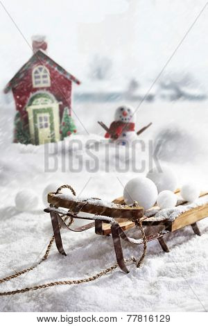 Wooden sled and snowballs with snowman and wintery background