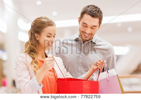 sale, consumerism and people concept - happy young couple showing content of shopping bags in mall