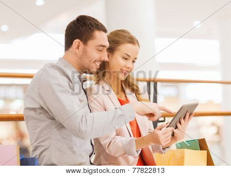 sale, consumerism, technology and people concept - happy young couple with shopping bags pointing finger to tablet pc computer in mall