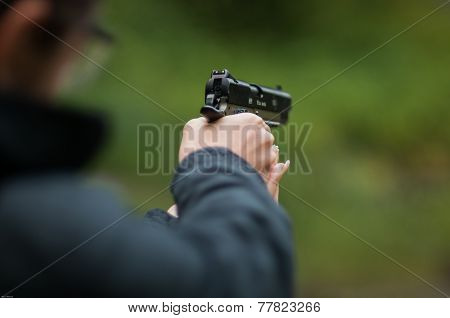 Blurred woman holding a gun and targeting