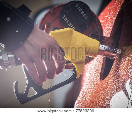 Hand refilling the car with fuel, close-up.