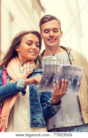 travel, vacation, love and friendship concept - smiling couple with city guide exploring town