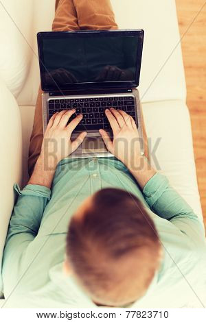 technology, leisure, advertisement and lifestyle concept - close up of man working with laptop computer and sitting on sofa at home
