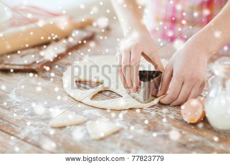 cooking, baking, people and home concept - close up of woman hands making cookies from fresh dough at home