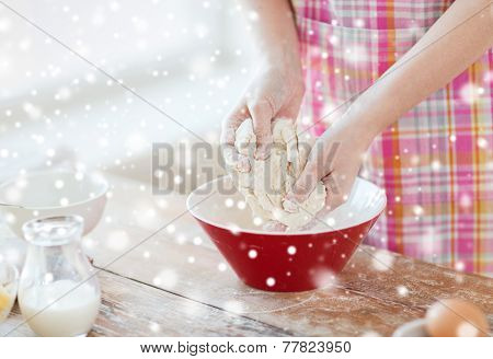 cooking, baking, food, people and home concept - close up of female hands kneading dough in kitchen
