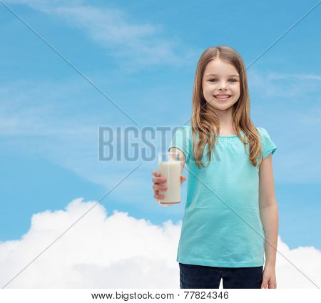health and beauty concept - smiling little girl giving glass of milk