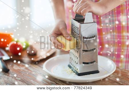 cooking, food, people and home concept - close up of female hands with grater and vegetables grating cheese in kitchen