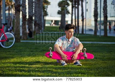 Young hipster man sitting on the grass with longboard