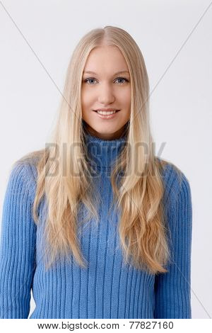 Portrait of young blonde woman smiling happy, looking at camera.