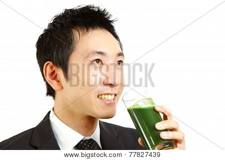 businessman drinks green vegetable juice