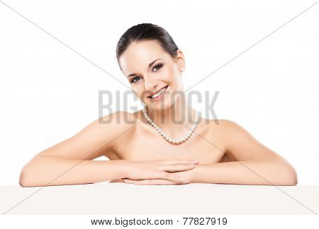Portrait of young, beautiful and healthy woman in a pearl necklace isolated on white