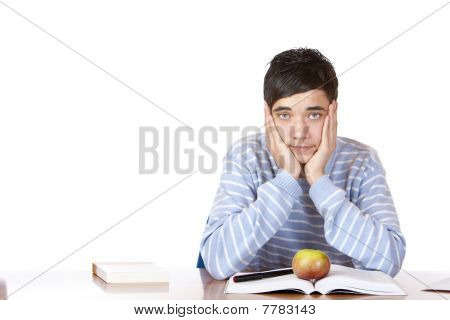 Young student sitting on desk and learns for his exams.