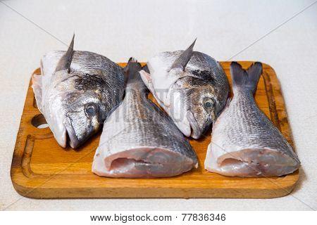 Dorado fish on a cutting board knife cut half