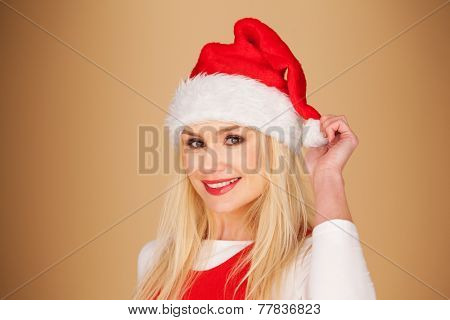 Merry young woman with shoulder length blond hair wearing a red Santa hat smiling happily at the camera as she celebrates Christmas, on a brown background with copyspace