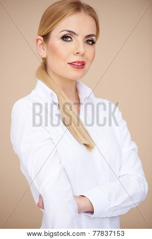 Close up Pretty Young Confident Woman with Blond Hair in White Long Sleeve Shirt with Collar  Crossing her Hand in Front her Body While Looking at the Camera. Isolated on Very Light Brown Background.