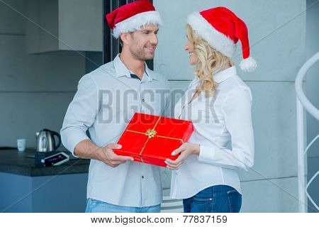 Couple Wearing Santa Hats Smiling at Each Other and Exchanging Wrapped Christmas Gift