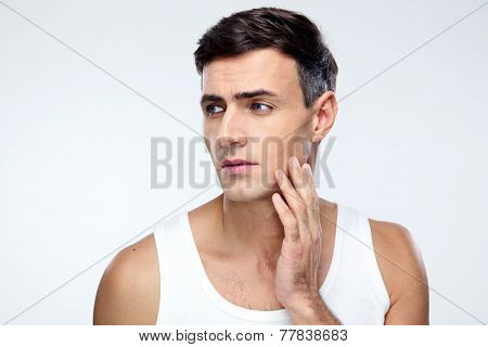 Pensive man looking away over gray background