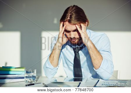 Tense businessman touching his head while looking at display of touchpad