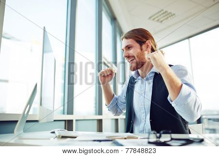 Ecstatic businessman looking at computer monitor in office