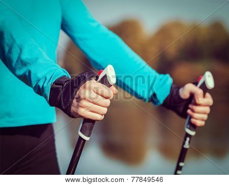 Vintage retro effect filtered hipster style image of nordic walking exercise adventure hiking concept - closeup of woman's hand holding nordic walking poles
