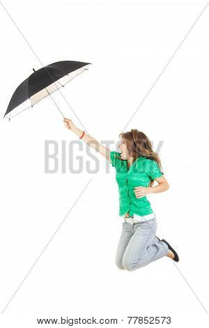 Surprised Young Woman Or Girl In Green Shirt And Gray Jeans Pants With Umbrella Jumping