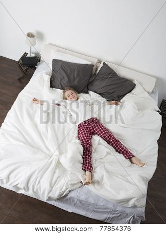 Happy Little Girl in a large bed from high angle view