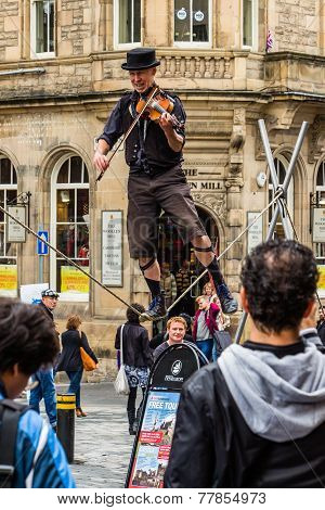 Street Performer On The Rope While Playing The Violin