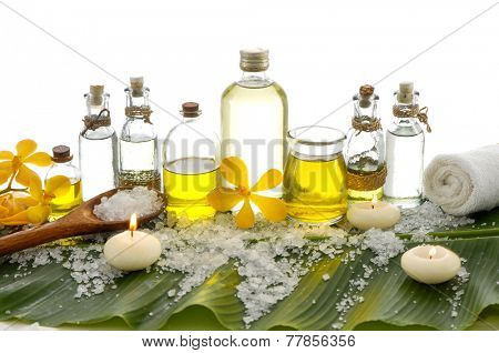 spa supplies with orchid, oil, candle ,soap salt on banana leaf