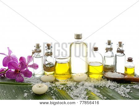 spa supplies with orchid, oil, yellow candle , salt on banana leaf