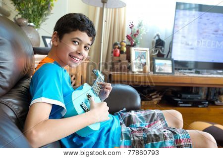 Young pan asian boy practicing on his blue ukulele in a home environment