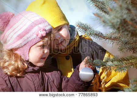 happy children decorating New Year tree with toy balls in park