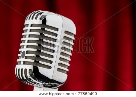 an old retro microphone in front of red velvet background.