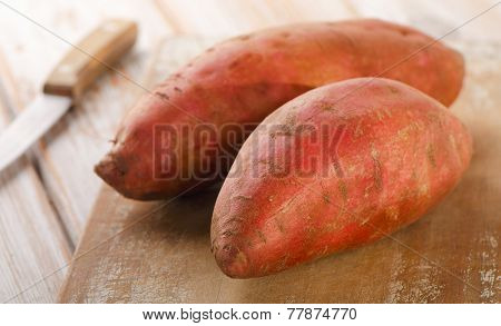 Raw Sweet Potatoes On Wooden Background .