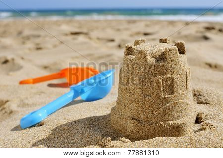closeup of a sandcastle and toy shovels of different colors on the sand of a beach